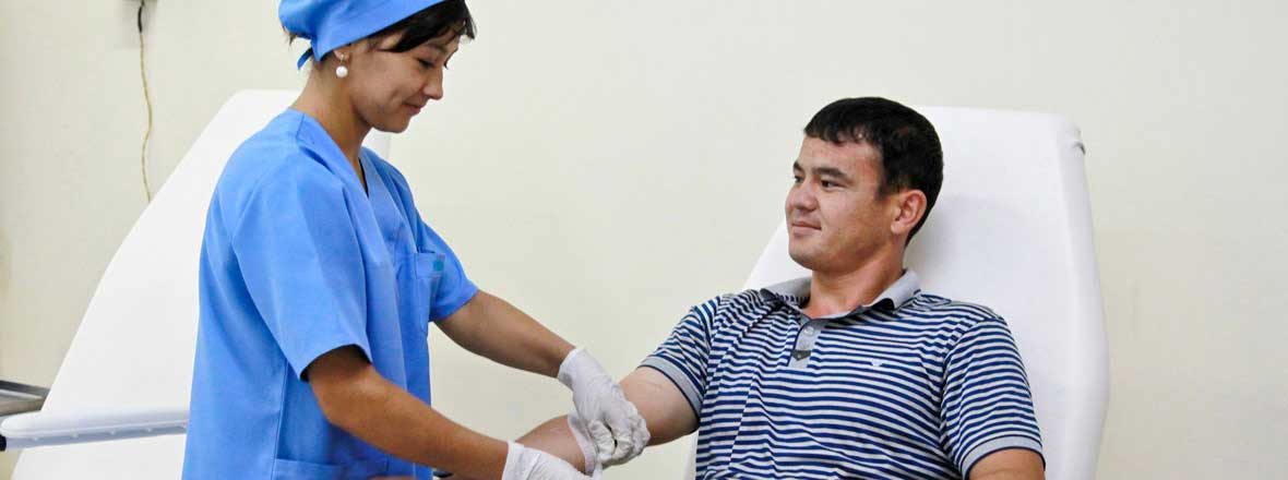 image of female nurse taking blood sample from male patient