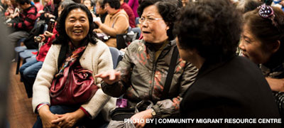 Image of four Asian-Australian women talking at crowed community event